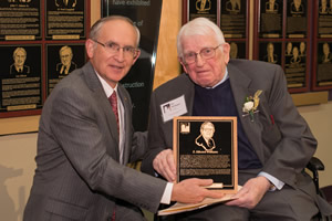 Ferris State University president David Eisler presents the Michigan Construction Hall of Fame Award to E. Edward Williams.