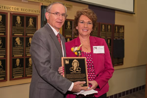 Ferris State University president David Eisler presents the Michigan Construction Hall of Fame Award to Linda Vos-Graham.