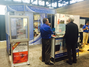 Polytronix's Timothy Connell discusses the company's privacy and LED switchable glass with a fellow exhibitor Thursday.