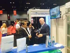 Pleotint's Geoff Brown explains the energy-saving benefits of Suntuitive, the company's self-tinting windows, with fellow exhibitors Thursday.