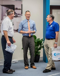 Origin president Ben Halvorsen (center) talks with Venice Chamber of Commerce CEO John Ryan and Venice mayor John Holic at the local opening of Origin's new U.S. headquarters in April. (photo: Origin)