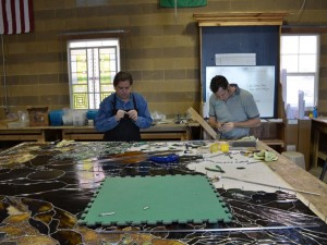 Holdman Studio's Tom Holdman and Cameron Oscarson work on the art glass project in their shop.