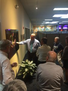 Cleveland artist Brian Jones, whose designs can be seen throughout the FeneTech facility, explains to guests the fractal design on glass.